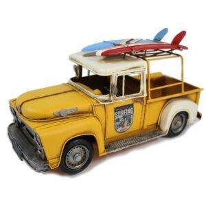 Camion en métal jaune et planche de surf